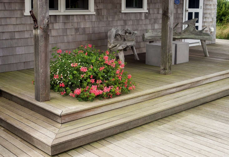 A colorful foil for the gray, weathered shingles on the porch of the original structure, Tim employed another signature element: generous and vibrant planters, this one planted with hot-pink Geranium &#8