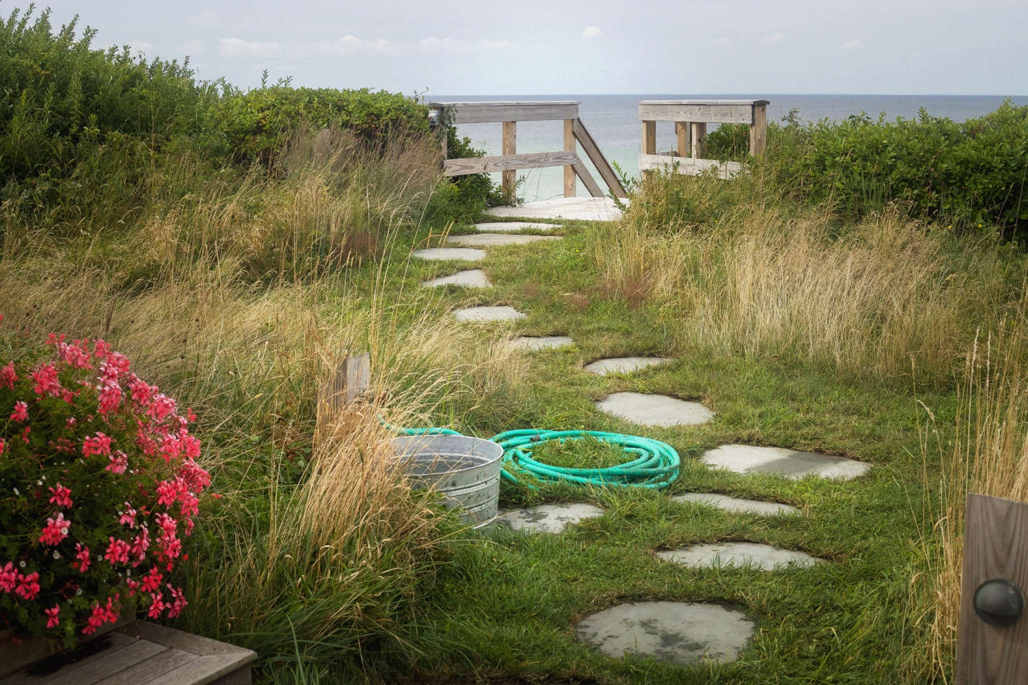 From the courtyard a traditional stone path leads to the steps down to the beach. One of our favorite informal elements is the simple hose and galvanized tube for washing sandy feet.