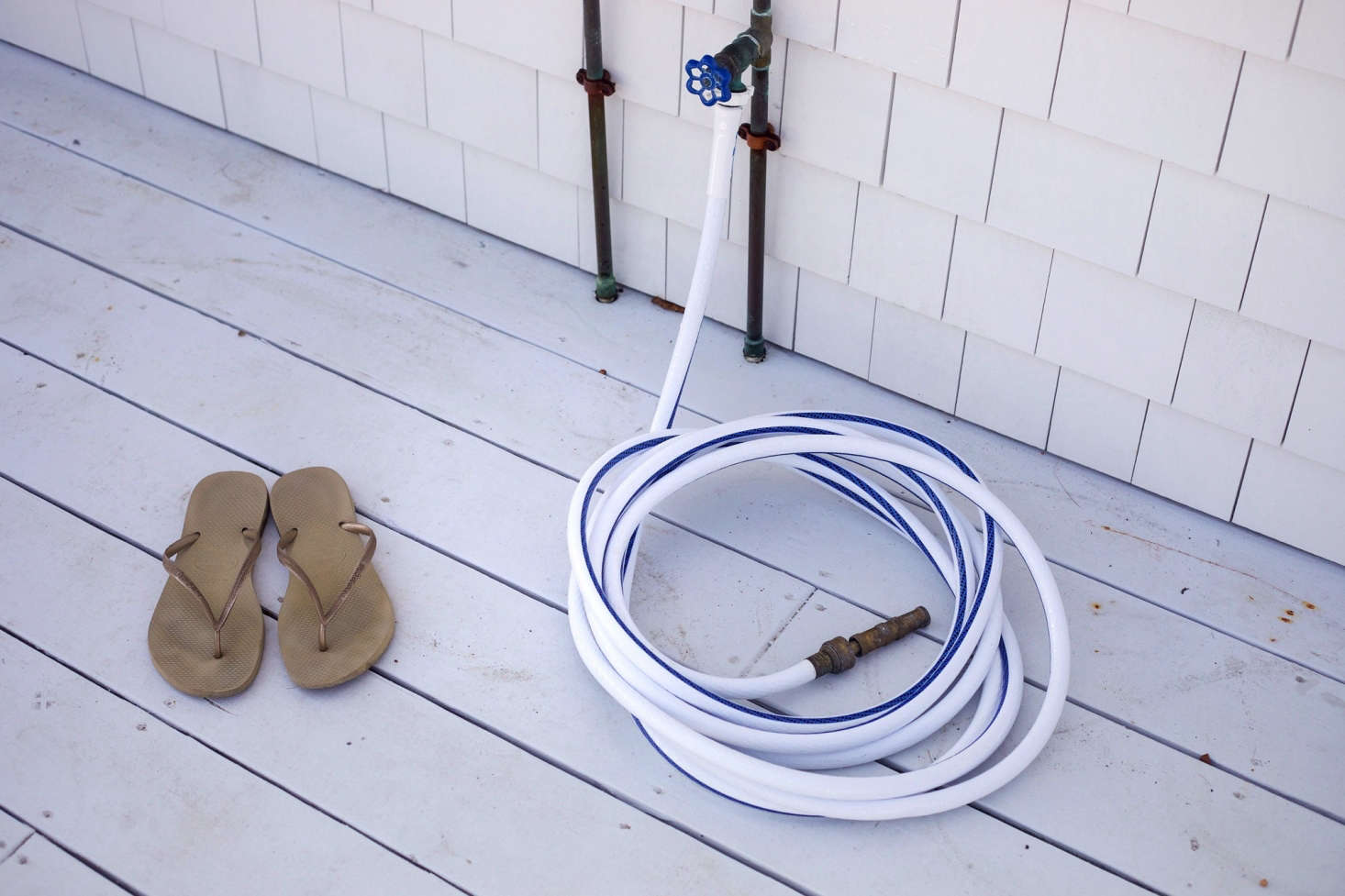"No space for an outdoor shower? A simple hose will do for rinsing grass cuttings from feet. Or, place a shallow bucket full of water beside the door for a quick dip. Photograph from Shipshape Cape Cod Cottage Inspired by Wes Anderson's ""The Life Aquatic&#8"