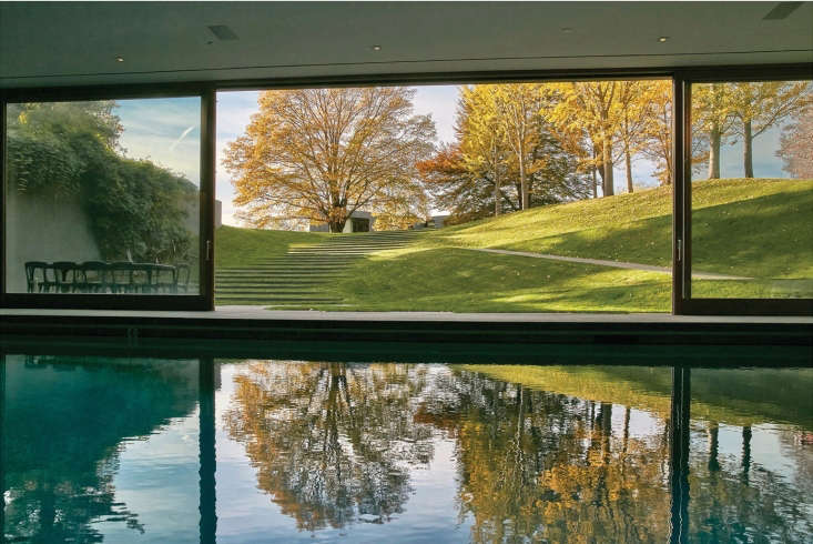 The view from inside the pool house frames a view of deciduous trees turning a fiery yellow and orange in autumn.