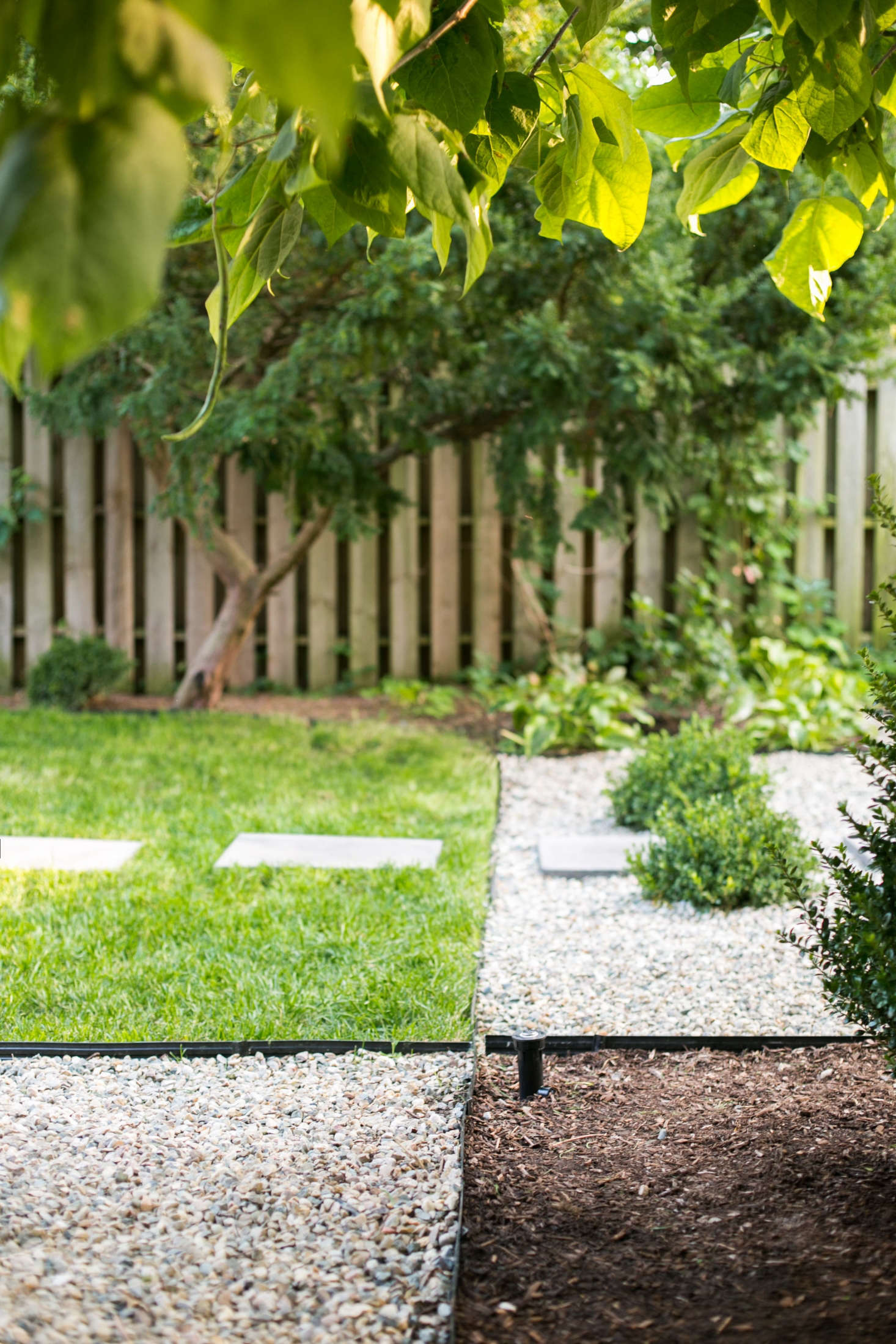 Contractor Packard came up with a landscape design that integrated turf grass (for the dogs to play), gravel (to edge pathways, and mulch (as ground cover beneath shrubs and other plants).