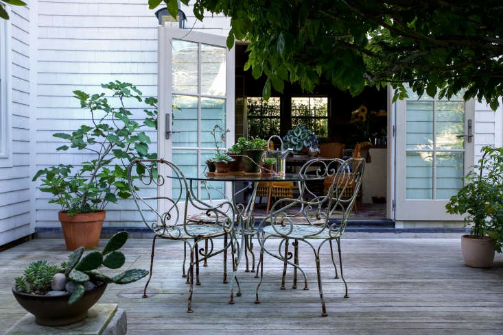 """Like the front yard, the backyard is an extension of living space, with French doors that connect the kitchen to the outdoors. """"We love having all the doors open so that the interior merges with the exterior,"""" Kristin says."""