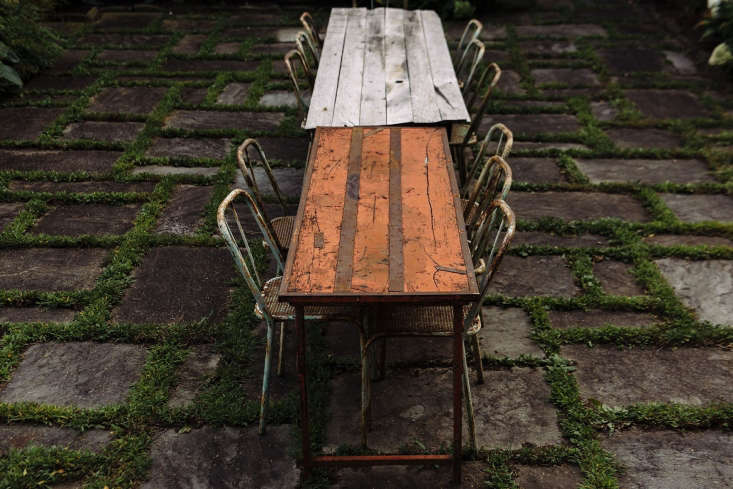 One-of-a-kind vintage dining tables sit end to end on the patio.