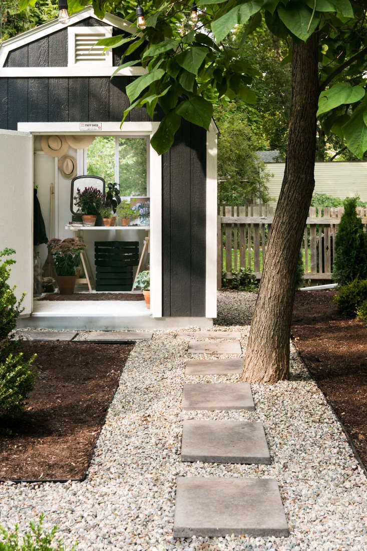 A shed tucked into the back corner of the garden is linked visually with a path of pavers set in gravel. Adams installed a customized Tuff Shed from Home Depot, matching the facade color to the exterior paint on her house.
