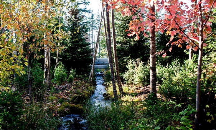 A granite bridge capable of supporting vehicles spans a restored stream. &#8\2\20;A gravel entry drive crosses the restored stream over a new granite bridge. The dwellings are one-story from the road, embedded in a grove of red maples and native birches,&#8\2\2\1; says Stimson.