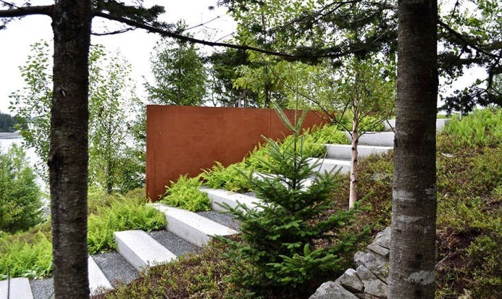 A steel wall at the edge of a stairways of granite pavers and gravel blends into the natural surroundings. New plantings include trees (birch, poplar, and spruce) and perennials (hay-scented ferns, and blueberry and huckleberry bushes).