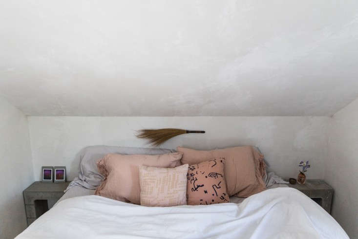 """In their so-called """"Soot House,"""" Anthony Esteves and Julie O'Rourke display an antique broom over their bed. See more in The Soot House: Conjuring the Ghosts of Old New England on Spruce Head in Maine. Photograph by Greta Rybus."""
