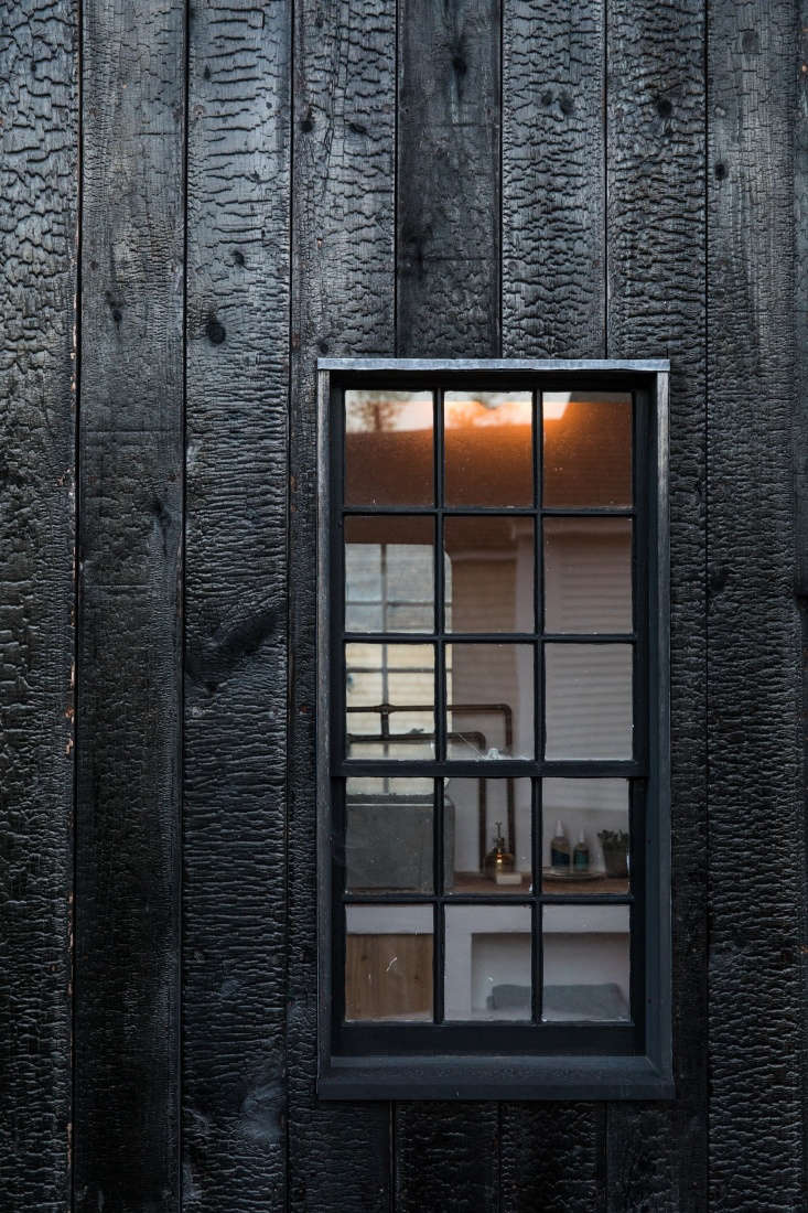 A detail of the charred-wood siding and windows with black mullions.