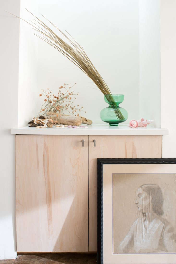In a small vignette at the top of her stairs, Sophia used a green vase with grass she found in an abandoned lot next to a train station. (&#8
