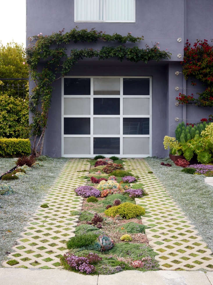A ribbon driveway has permeable pavers and a planting bed of succulents and low-growing ground covers. See more at Required Reading: Private Gardens of the Bay Area. Photograph by Marion Brenner.