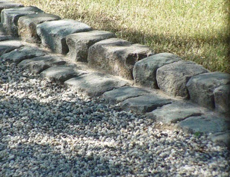 Antique granite cobblestones edge a lawn. For prices and information, see Historic European Cobblestone.