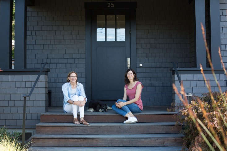 Haegglund (L) and Raleigh Zwerin sit on the front porch, where Arts and Crafts-inspired architectural accents include paired columns, a front door with window panes, and a waist-high railing.