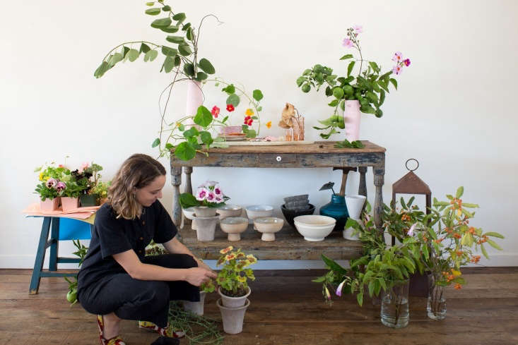 Sophia works with a geranium near a vintage wooden table that she uses as an artist&#8