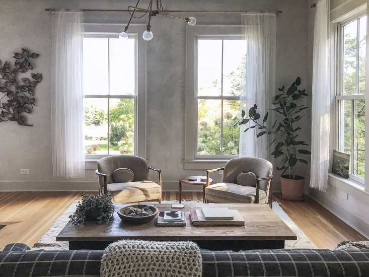 In a room with high ceilings, twin windows are flanked by foliage, both faux and alive. The shape and texture of a potted Ficus elastica&#8