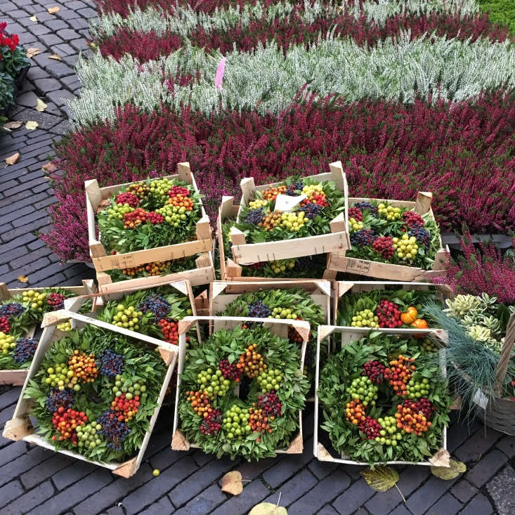Seasonal wreaths and fall-blooming heathers carpet the square.