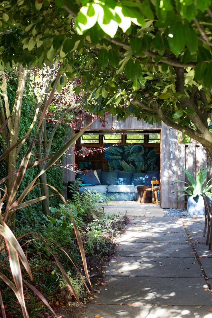 In the side garden is a dining patio and a cottage, nicknamed the Blue Agave Lounge and tucked into a corner of the property;a roll-up wall of windows invites breezes.