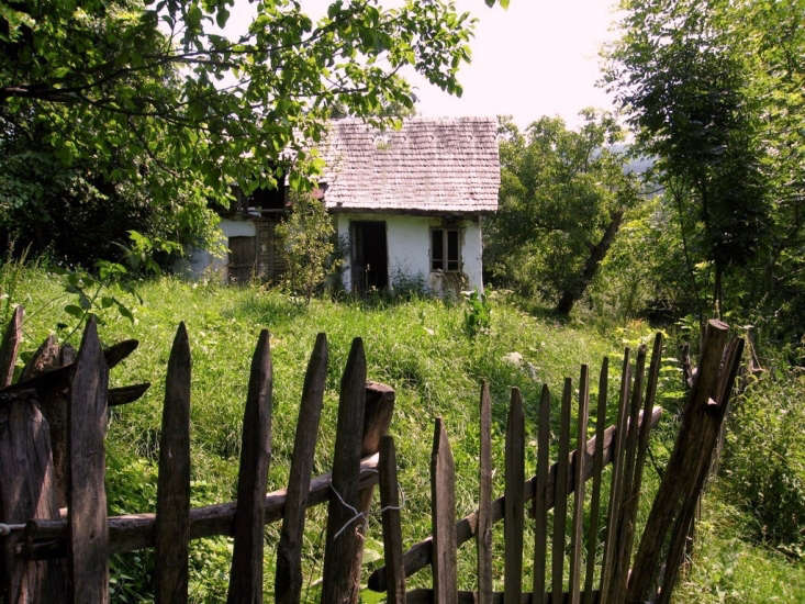 In Comarnic, Transylvania, a rustic wooden fence and fruit trees surround a cottage. Photograph by Dag Terje Filip Endresen via Flickr.