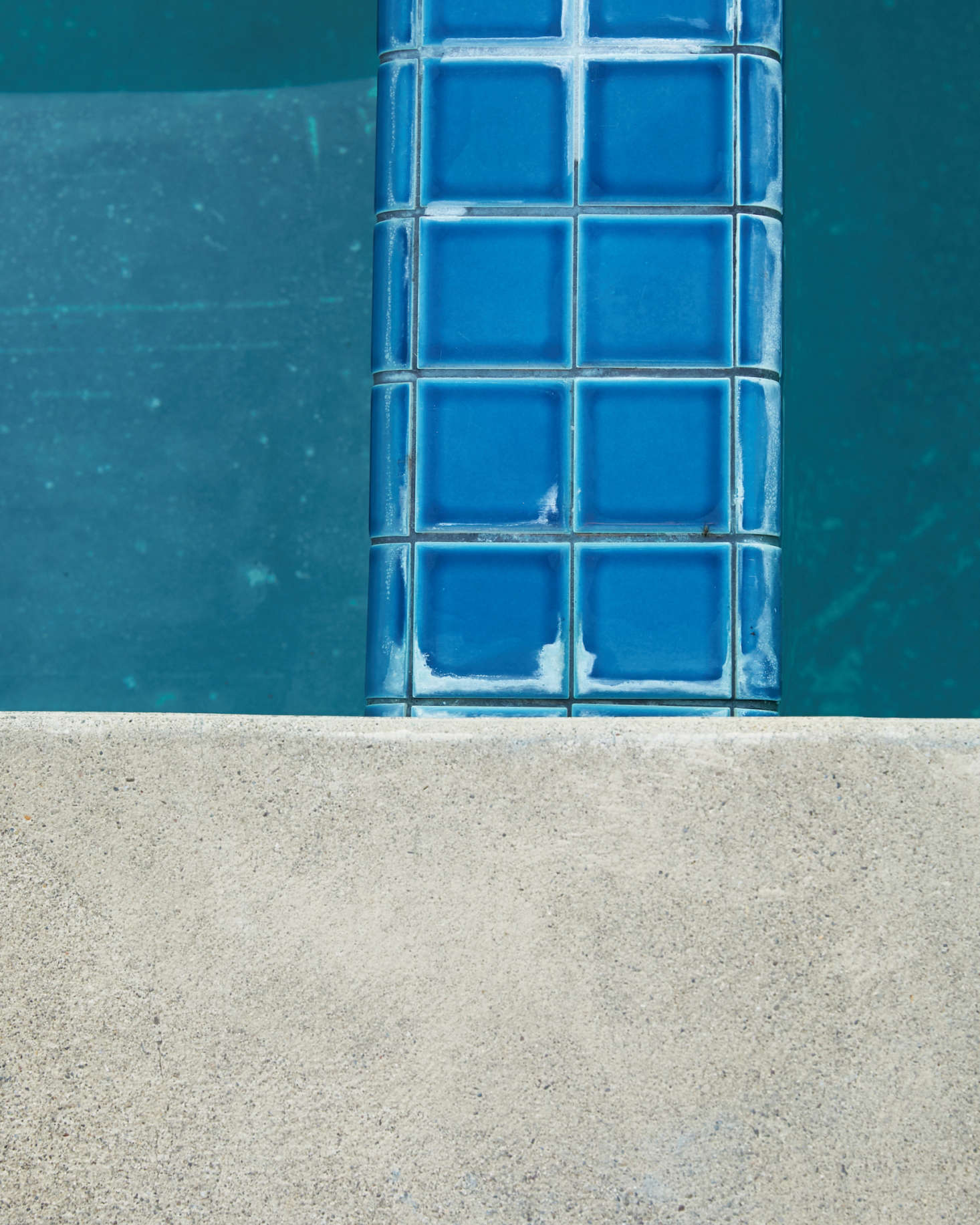 Bright turquoise tiles and a pale concrete deck define space in and around the dark teal pool.