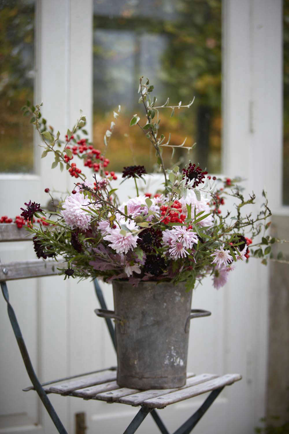 An early winter arrangement with red berries of cotoneaster, handfuls of rosemary, and dark scabious &#8