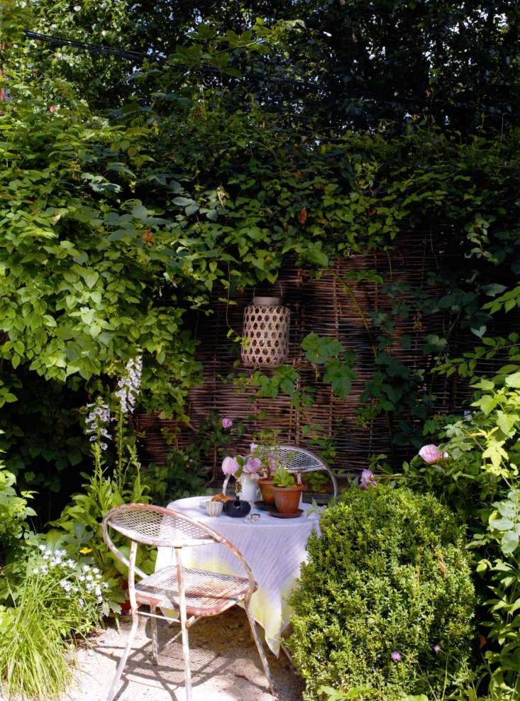 A small dining nook with vintage metal chairs is fenced off with woven hazel hurdles and lit with simple lanterns.