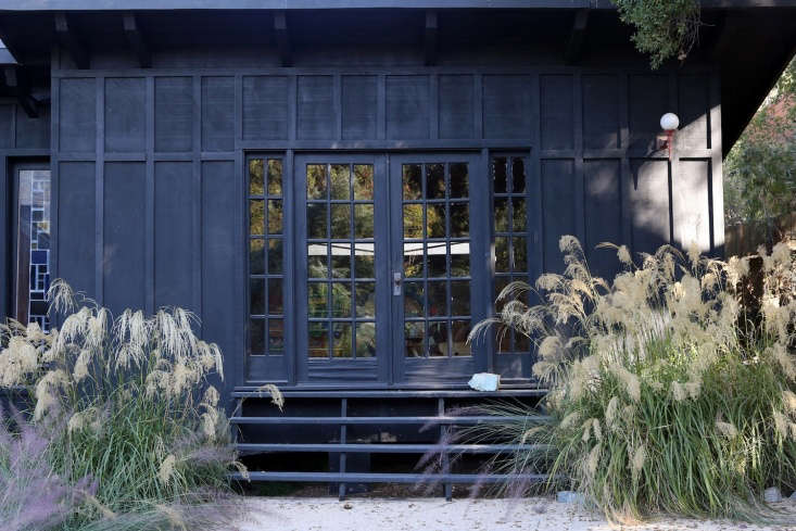 Two white grasses flank a short stairway and French doors on one end of the house.