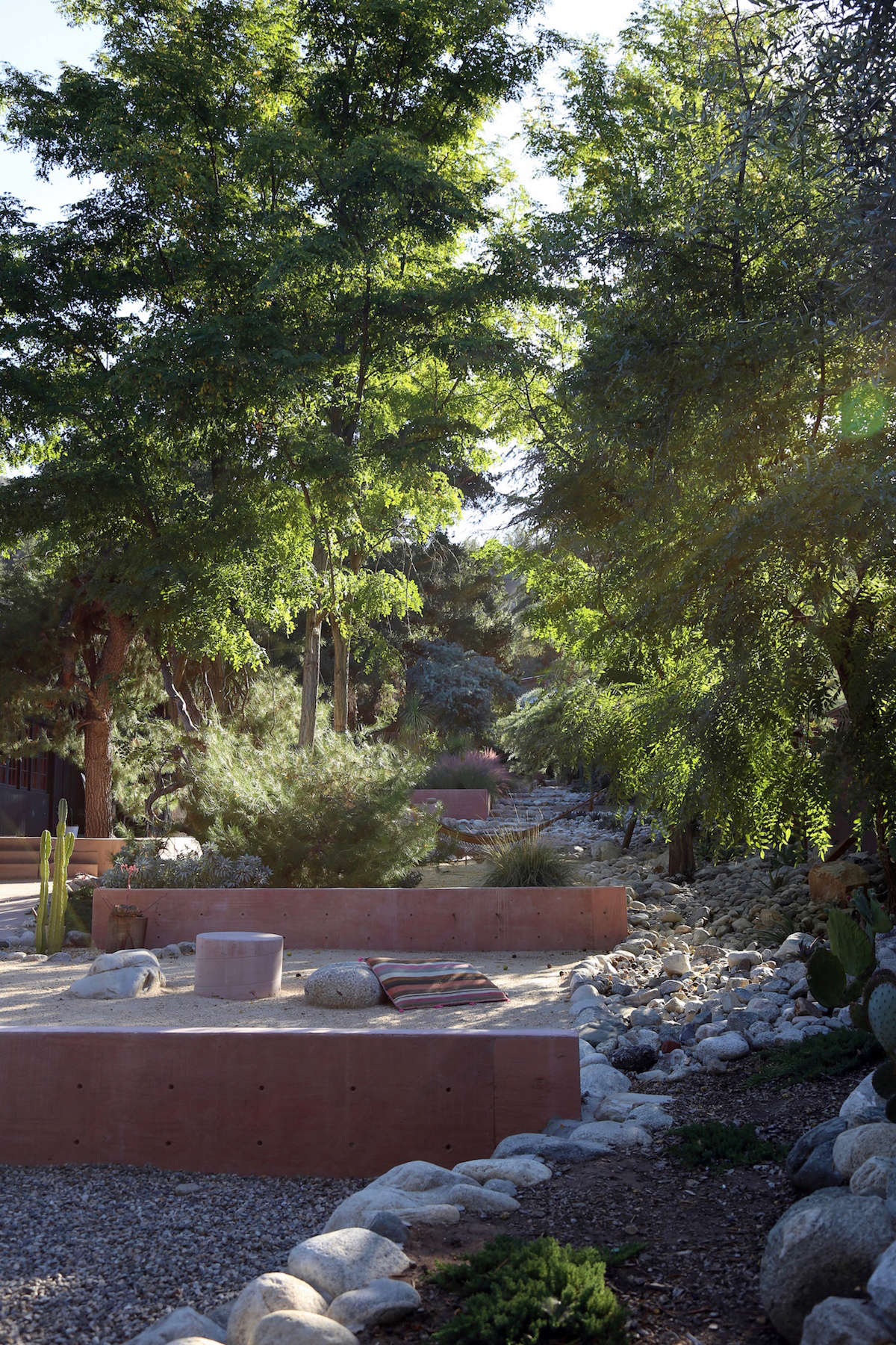 The Morgans created a rock river along one side of the garden, composed of small boulders they collected over time. The largest stones, including those used as seating around the small pink concrete table shown above, are from Southwest Boulder & Stone.