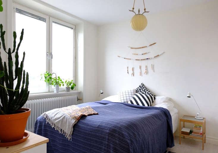 The bed faces the plant wall, which receives plenty of natural light. The interesting ceiling light came with the apartment. Maria made her branch wall hanging using paint and blue thread.