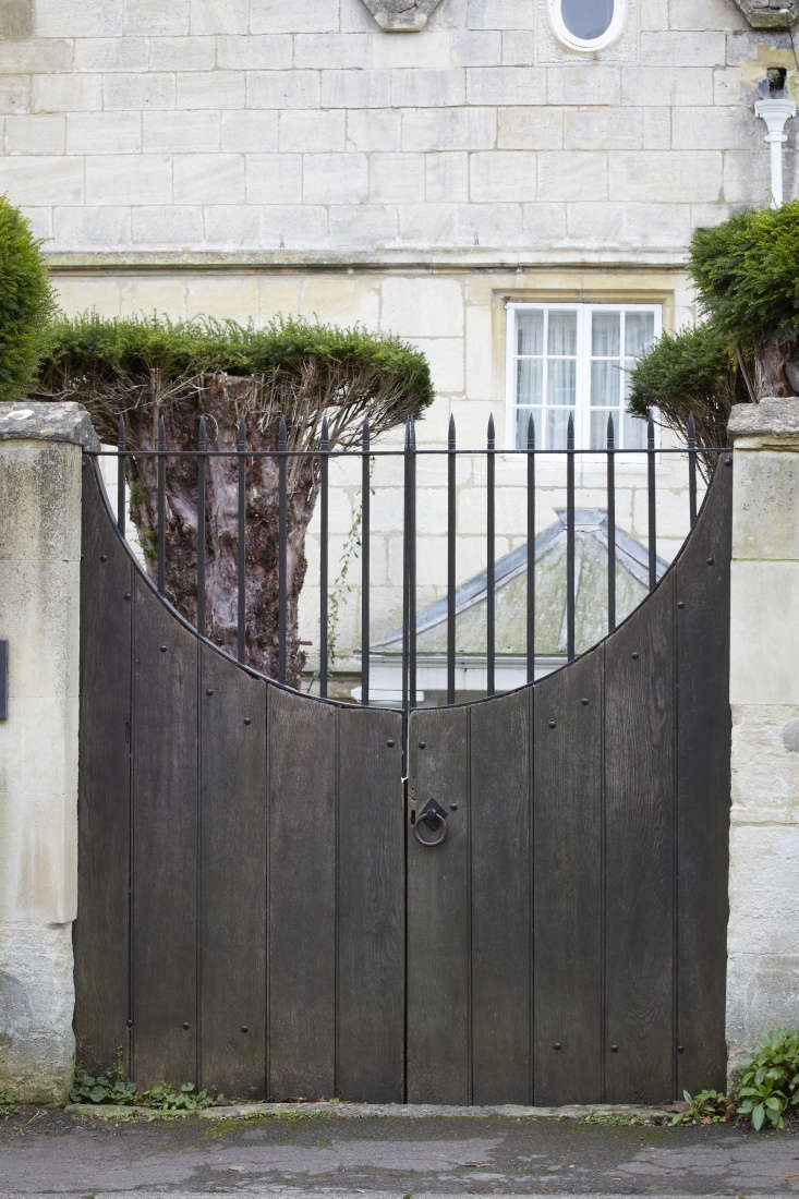 Half-moon gates are generally inviting to the casual snooper, but this one has a sting in the tail, with wrought iron spikes filling in the empty space. This gate says yes, you may look, but don&#8
