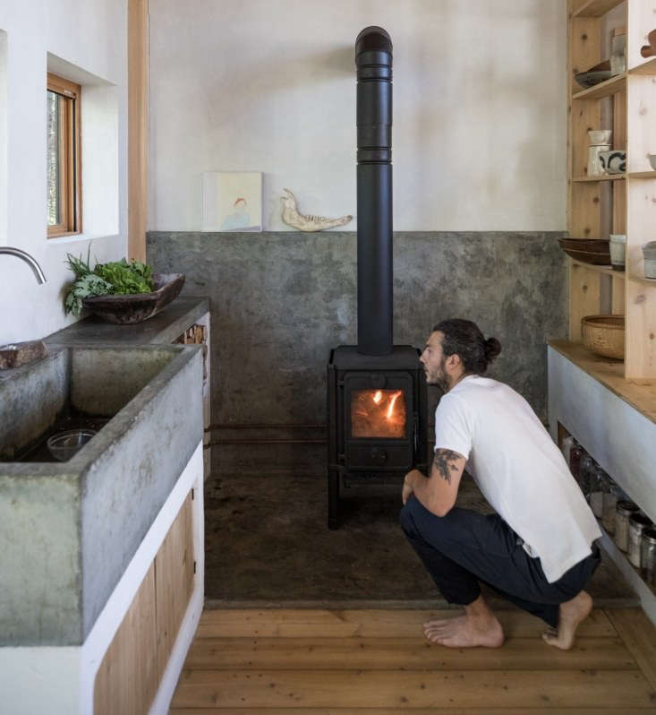 In a kitchen designed &#8\2\20;with maximum efficiency in mind, particularly for the long Maine winters, heat from the woodstove—the house's only heat source—rises through the ceiling into the sleeping loft above, then is pulled back downward through a floor grate to create a convection heating system for the whole house,&#8\2\2\1; writes Annie. Photograph by Greta Rybus.