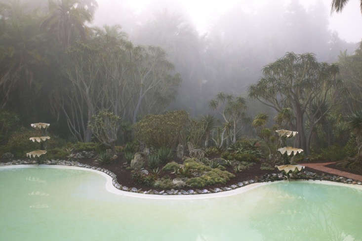 The sea green pool betrays its origins as a swimming pool through its retro kidney shape.