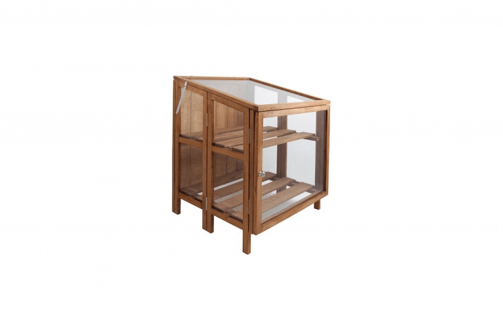 AHardwood Small Greenhouse by Esschert Design has glass panel walls, a hinge flap, and two adjustable shelves; \$\269.99 from Amazon.