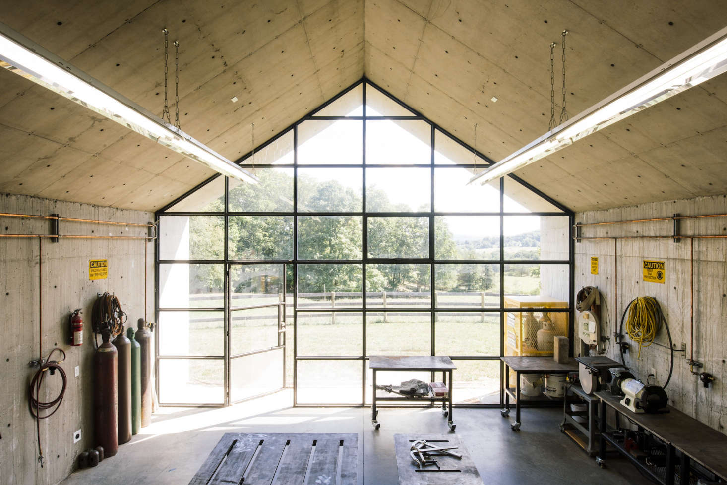 At one end of the studio is a gabled wall of gridded steel windows with embedded lights and an operable door. The studio is lighted by two long rows of off-the-shelf fluorescent hanging lights.