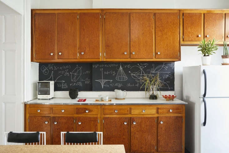 """Architect C.S. Valentin treats his Brooklyn apartment like a science lab; seen above is a backsplash he cobbled together from a slab of wood covered with chalkboard paint. The math formulas &#8\2\20;contribute to the kitchen's investigative effect."""" Photograph by Jonathan Hökklo."""