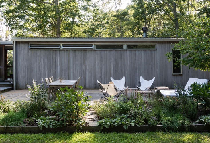 A simple patio adjacent to a house on Shelter Island, New York creates living and dining space outdoors.