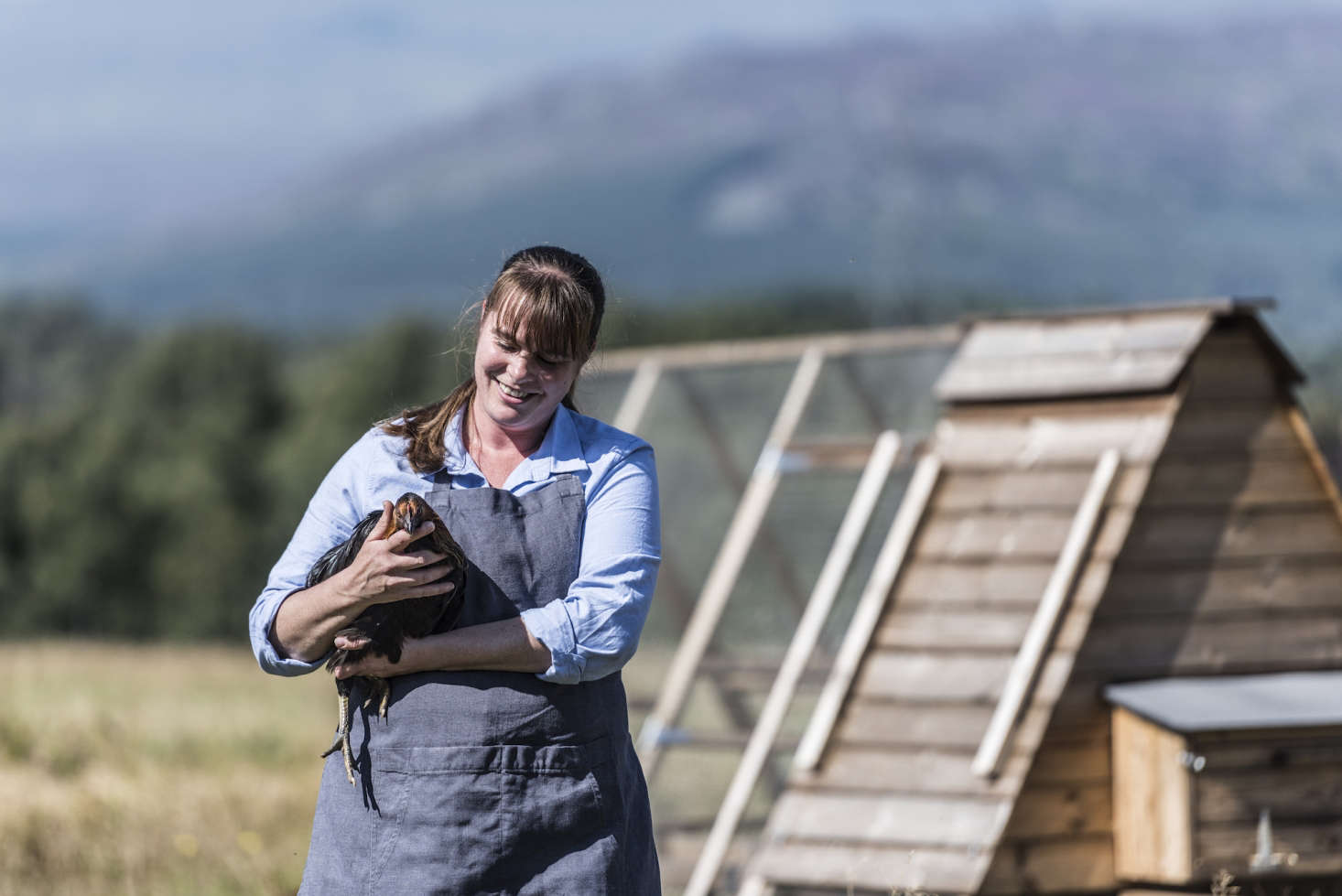 A farmer with an egg-laying hen.
