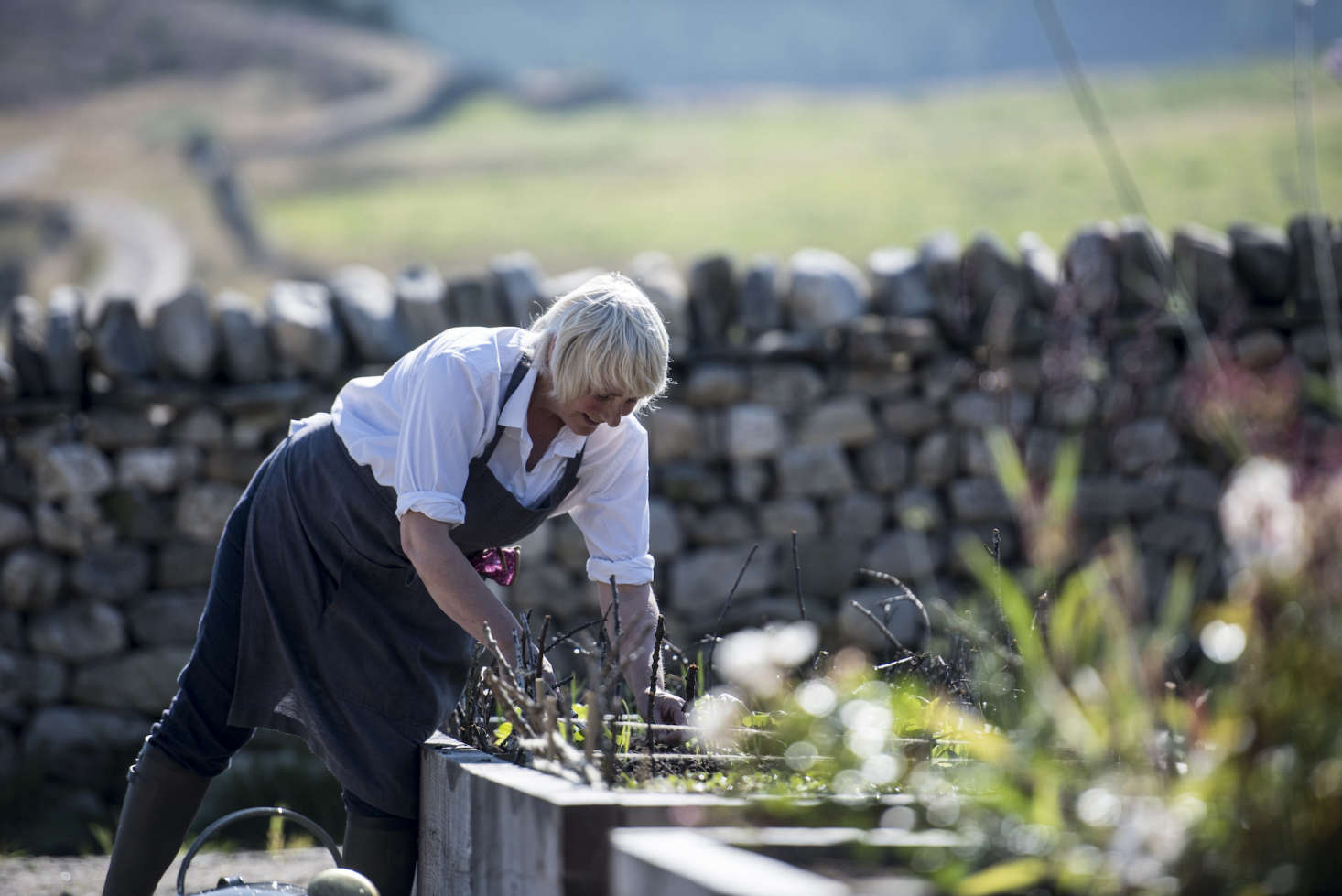 A farmer (fittingly, wearing wellies and a linen apron) tends to the vegetable patch.