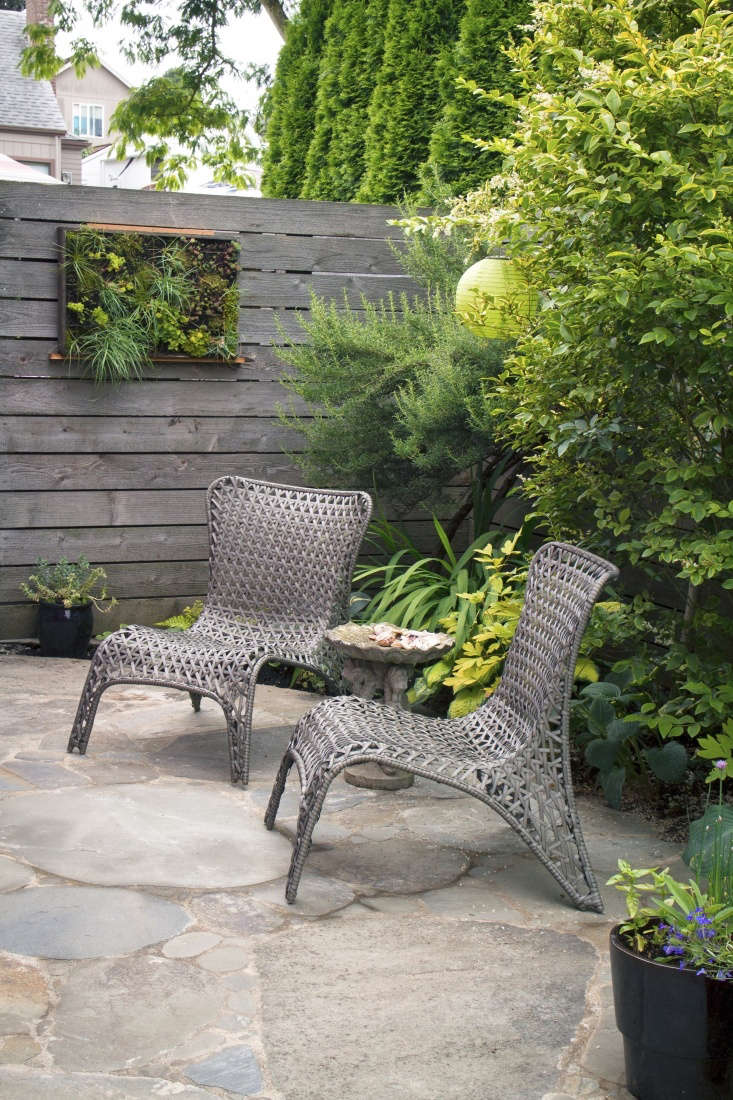In a small garden, two chairs and a side table are all the furniture you need to create an outdoor living room.