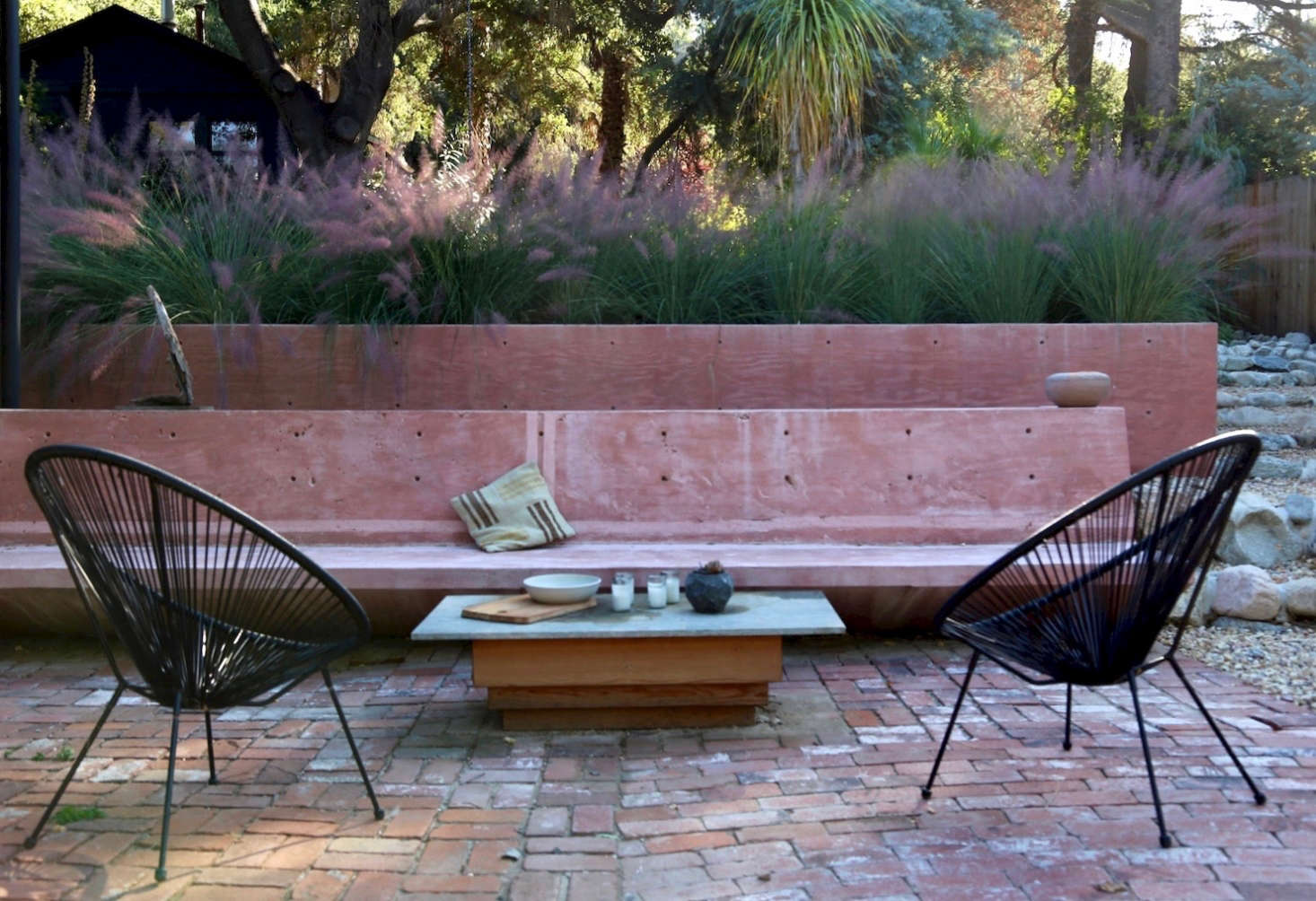 A long concrete bench juts out from the house, and defines the brick patio as an outdoor room. Matthew Morgan made the coffee table, which has a wood base with marble slab top. The black Acapulco chairs are from a garden store at the base of Topanga Canyon.