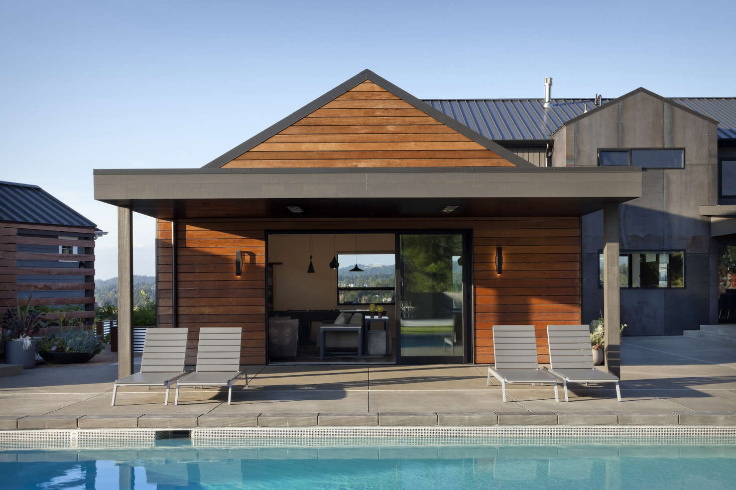 A media room is attached to the house but functions as an indoor-outdoor space during parties on the patio. Sliding glass doors open onto the pool deck, and a flat overhang creates shade for lounge chairs. The overhang and trim is paintedin Iron Ore from Sherwin-Williams.