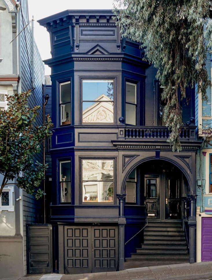 A dark blue facade, accented by glossy black trim, lends the house an elegant air.
