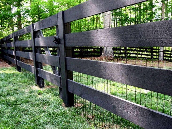 Black wire-mesh fencing is attached to four-by-four sawn board fencing. For more information and prices, see North Georgia Fencing.