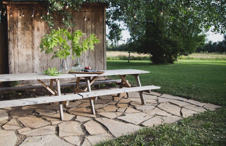 Blogger and interior designer Carmella Rayone hired someone to dig up the lawn, but otherwise constructed this patio herself—with help from her sons and husband. Photograph by Carmella Rayone, courtesy of Carmella Rayone, An Assortment, from Landscaping Ideas: A DIY Flagstone Terrace for $500.