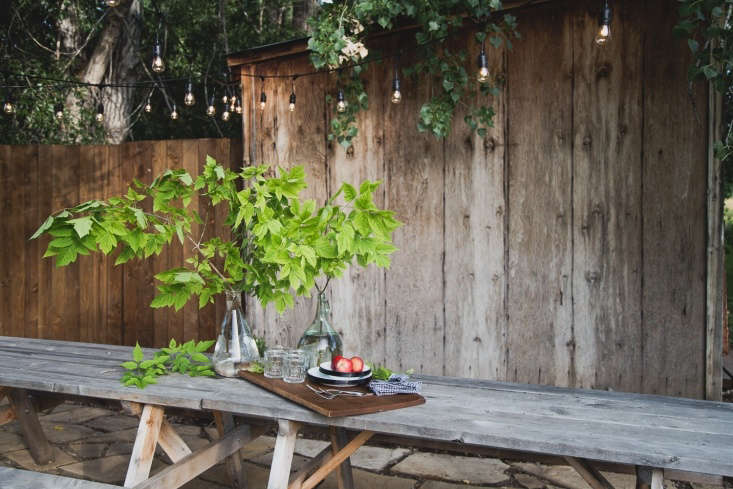 The trees provide shade, so no umbrellas are necessary, but to string globe lights evenly across, Carmella inserted black-painted conduit pipes at the corners. The shed will next be planted with New Dawn roses and clematis on a trellis.