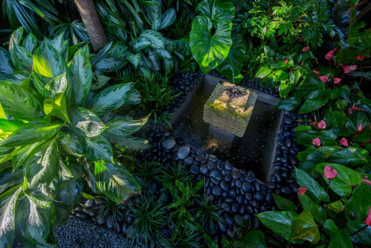 A water feature was sited to enable the owner to sit on the front porch and hear the sound of running water. Constructed of a square piece of oolite, as it ages the fountain will sprout ferns.