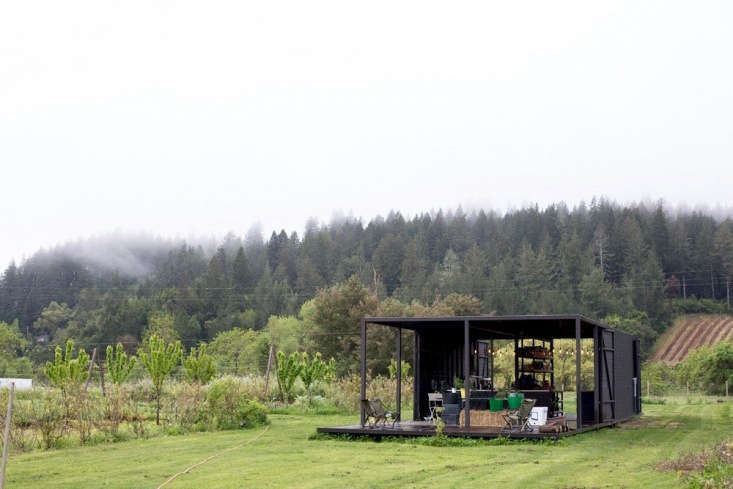 The open-air pavilion, complete with a working kitchen and fire pit, is a slatted wood structure that owes its stylish black exterior to a coating of pine tar and linseed oil, a water-repellant treatment widely used in Sweden to avoid the need to use pressure-treated wood.