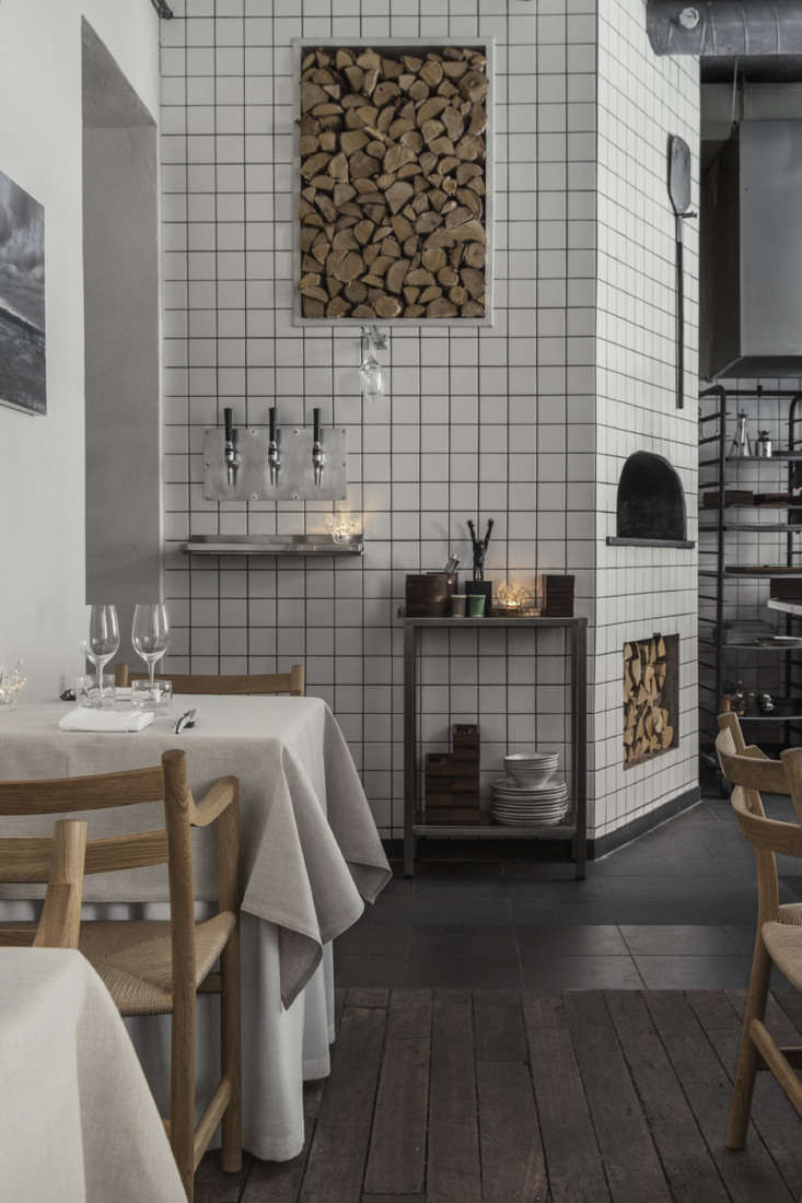 Firewood can be turned into art, as evidenced in the dining room of Agrikultur. Photograph by Niklas Nyman, courtesy of Agrikultur, from Steal This Look:  Design Ideas from a Tiny, Michelin-Starred Restaurant in Stockholm.