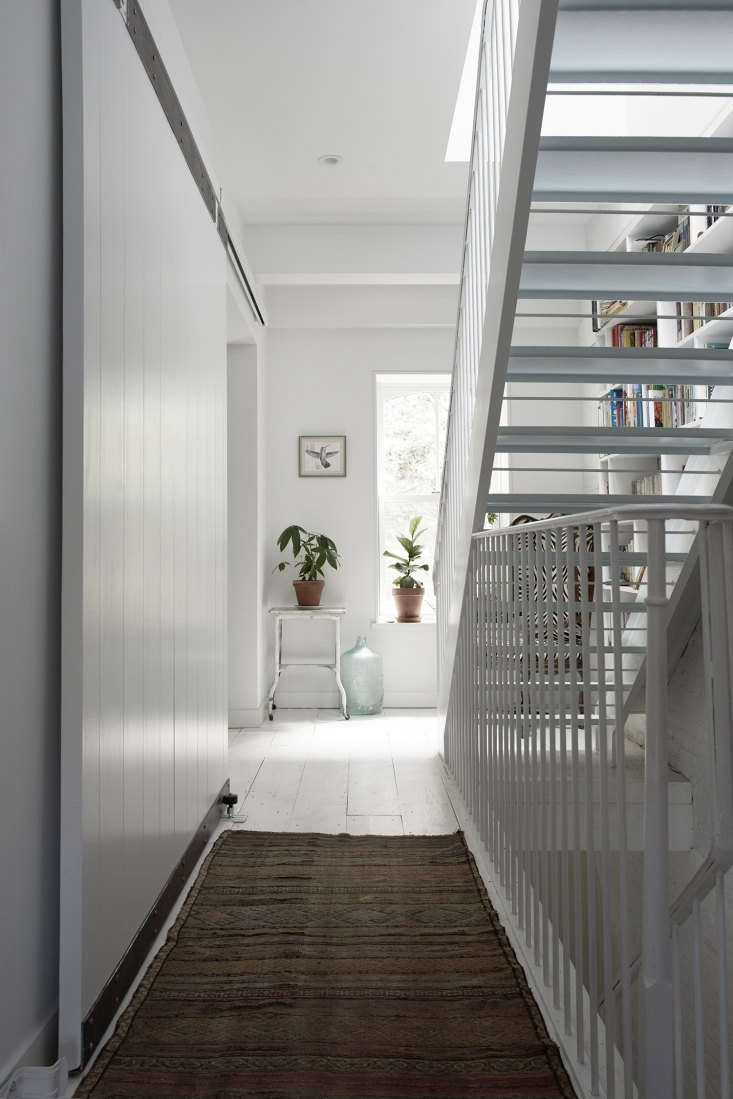 At the end of a long, narrow Brooklyn townhouse hallway, a pair of potted plants directs visitors toward the open doorway at the back of the house. Photograph by Pia Ulin, courtesy of white stair hall designed by Bangia Agostinho Architecture.