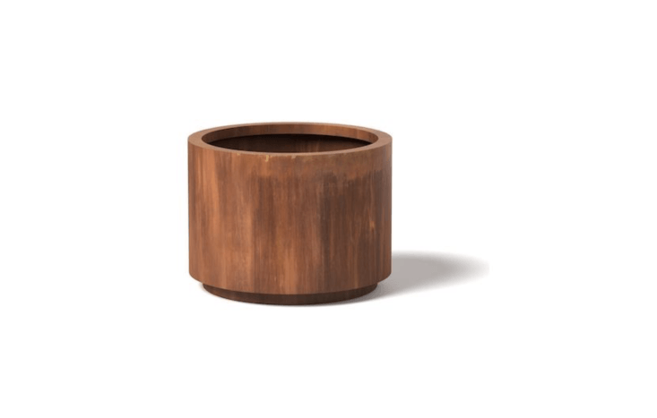 A \20-inch diameter Cor-ten Steel Cylinder Planter measuring \18 inches high has casters mechanically fastened to a recessed bottom, creating a \1/\2 inch- to 3/4-inch reveal between the deck and the bottom edge of the container; \$805 at Yard Art.