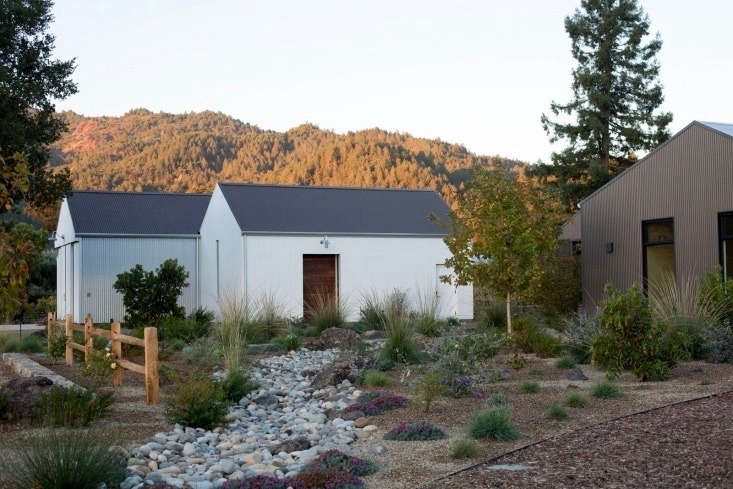At the Gallica vineyard, what looks like a compound actually is only two buildings: a \1,\200-square-foot white barn designed by St. Helena–based Daniel Hale Design and a \1,700-square-foot corrugated guesthouse with one bedroom designed by San Francisco–based architect E. B. Min of Min Day Architects and built by St. Helena-basedTeam Built Construction.