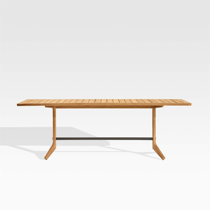The Kinney Teak Outdoor Dining Table, with a steel strut and trestle legs, is made of solid wood that&#8
